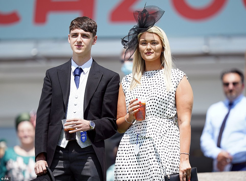 Polka dot perfection! Another woman posed it a spotted dress and sipped on a PImms for her day out at the races