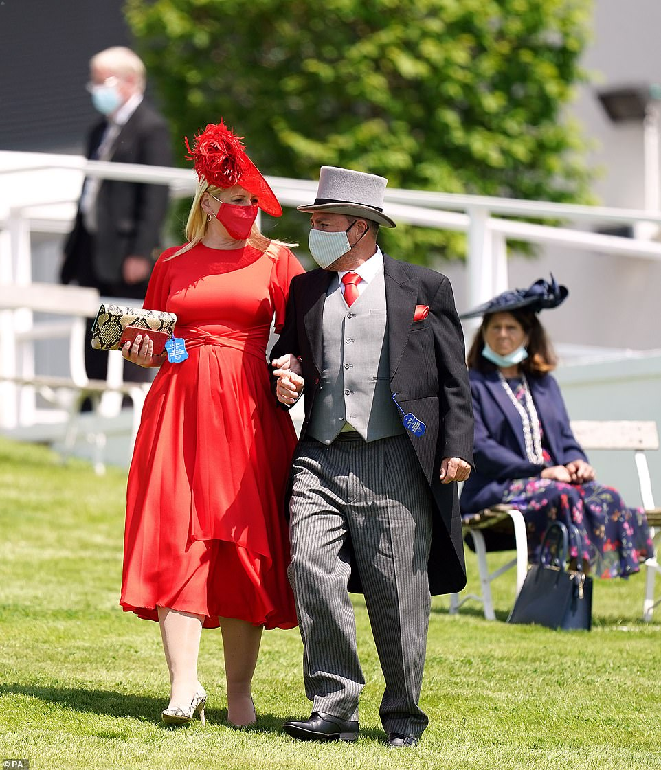 Lady in red! Another racegoer opted for a ankle length rouge number with a co-ordinating mask and hat to enjoy the sun