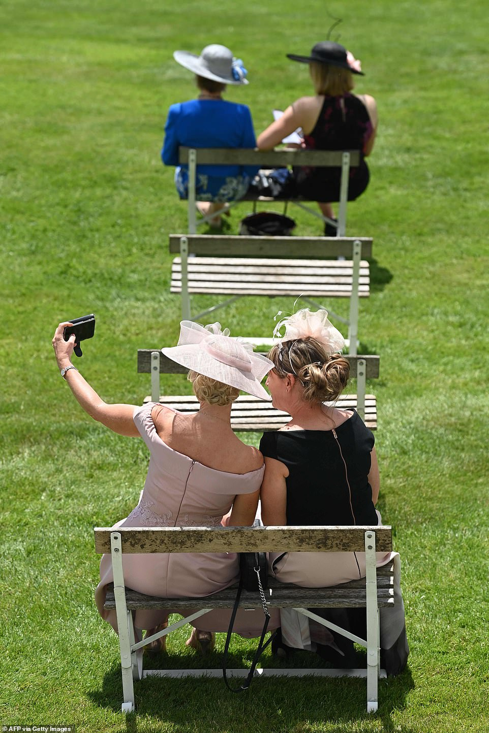Let me take a selfie! Two women posed for a selfie while sporting glamorous hats and gowns at the race course