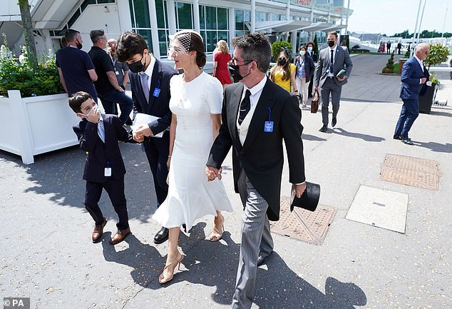 Elegant: Lauren looked effortlessly chic in a white midi dress and matching fascinator as she arrived hand-in-hand with Simon
