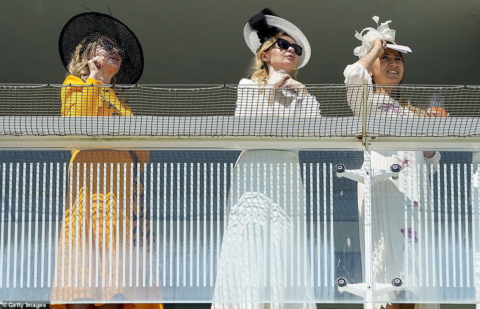 Three makes it a party! A trio of well-dressed ladies looked out to the horses while stunning in white and orange dresses