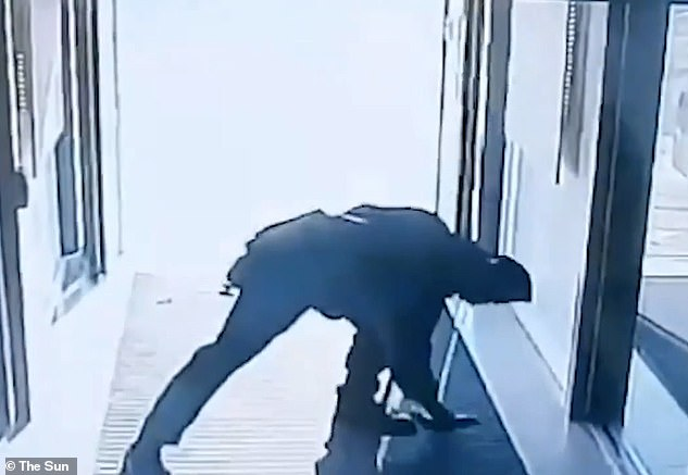 The man stops to pick up the weapon that has slipped out of his pocket before walking away