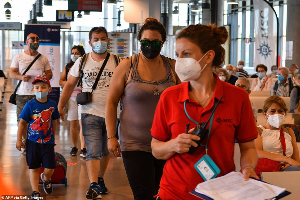 Passengers follow a hostess (R) as they go through boarding procedures prior to depart on June 05, 2021 aboard the MSC Orchestra cruise ship from the MSC Terminal in Venice