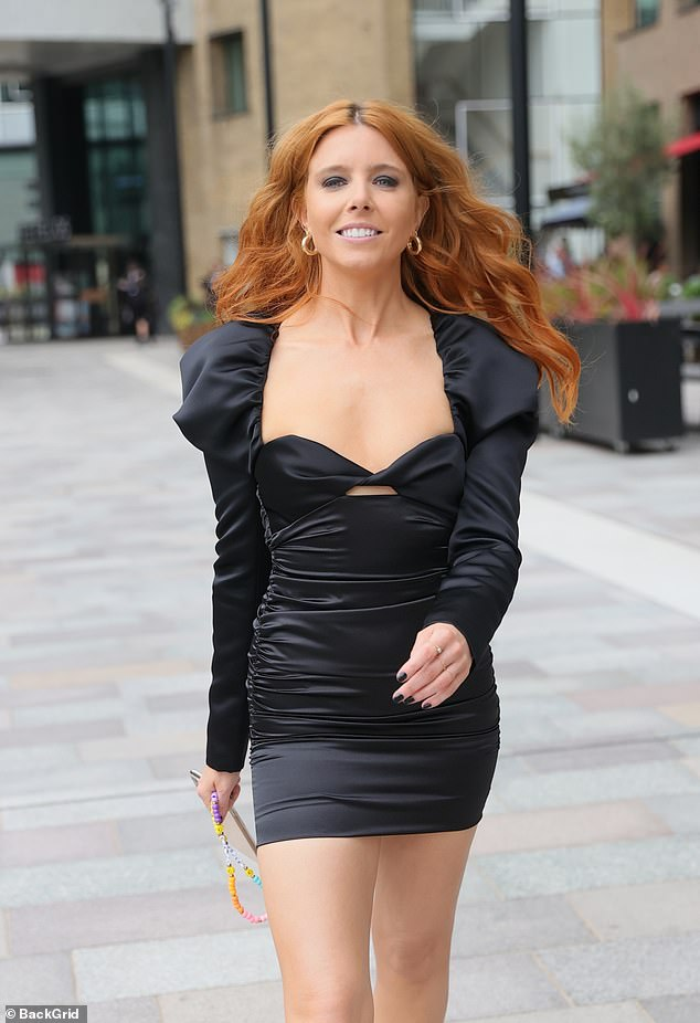 Beaming:The TV presenter, 34, put on a leggy display in a sexy black LBD which featured puff sleeves and a sweetheart neckline, while flaunting her toned pins