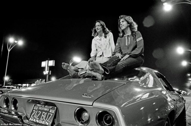 'Here it is: Perfect - couple of gals barefoot,' McCloskey said of the above image, adding that the car is a 1971 Camaro. 'I didn't go barefoot. I was doing a lot of shoe leather taking these pictures. I'd walk for miles.' Since it was Southern California, it wasn't unusual for people to be without shoes while hanging out. McCloskey, who grew up in the San Fernando Valley, recalled: 'The nights were long and beautiful. How do you beat it? Gee. I'm glad I was able to be part of that as a kid. It was really a formative experience'.
