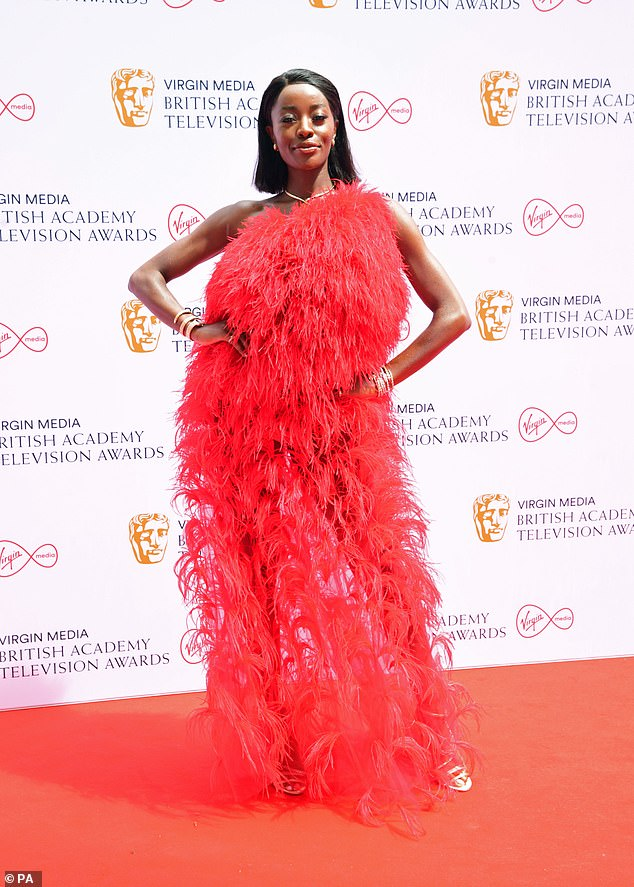 Flawless: AJ Odudu looked stunning as she stepped out on the red carpet in a red feathered one-shoulder gown at the BAFTA awards on Sunday