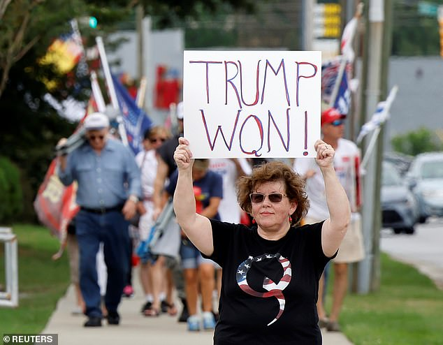 A supporter of former U.S. President Donald Trump wears a QAnon shirt while holding a sign stating he won the 2020 election outside his North Carolina rally on Friday