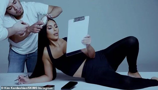 All hands on deck! Stylists fussed over Kim's look as she gazed at a clipboard