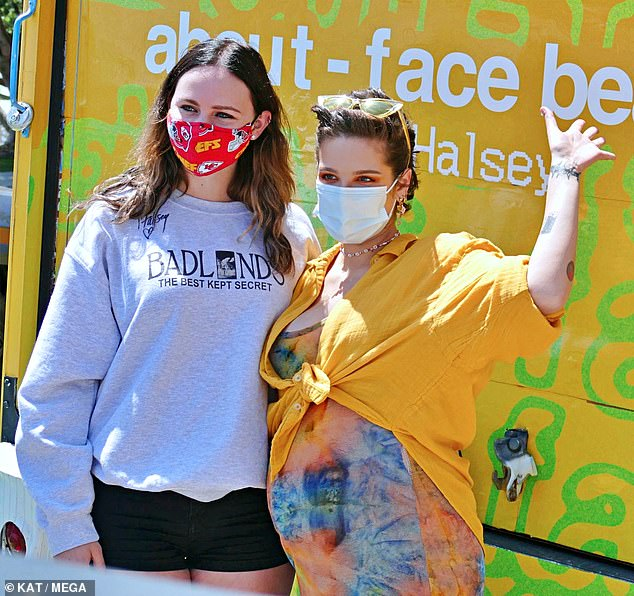 Staying safe: The hitmaker wore dramatic orange and yellow eye makeup from her line but kept her face covered with a blue surgical mask amid the ongoing COVID-19 pandemic
