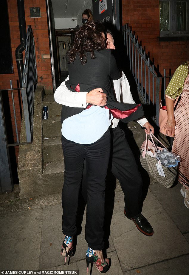 Loved up:She added a burst of colour with her floral heels and enlisted her boyfriend to carry her bag, which was laden with bottles of water