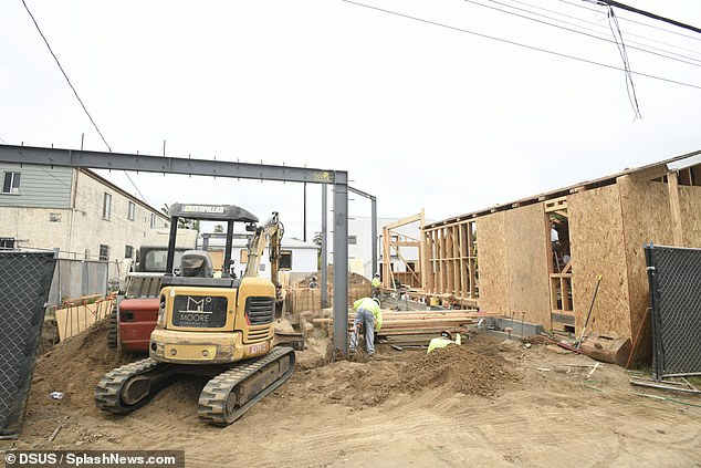 The show must go on: High-vis clad workers could be seen digging holes in the dirt, while other builders continued boarding up the skeleton of a half-built, wooden home