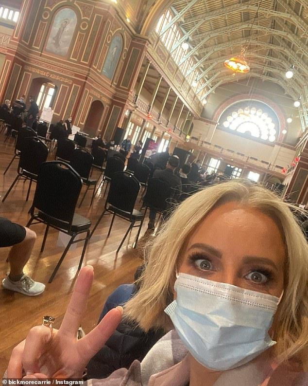 Peace out! Carrie posted this picture of herself wearing a mask while waiting for her jab in a Melbourne vaccination centre
