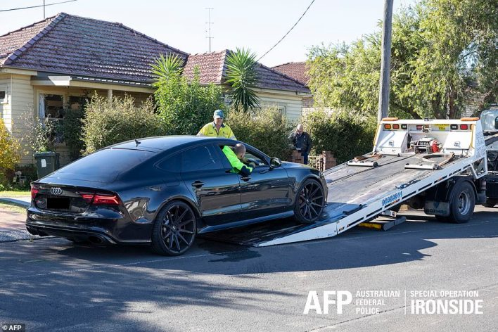 A blacked-out Audi coupe is loaded onto the back of a truck after being seized by the police