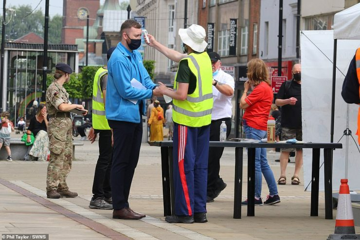 Surge testing will now be offered to members of the public all over Greater Manchester and Lancashire in a bid to stamp out a rise in coronavirus cases. Pictured: A man has his temperature taken in the street outside a vaccine bus in Bolton yesterday