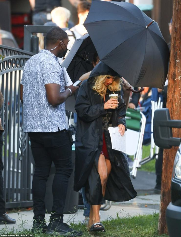 Getting ready for the role: Lily was seen being helped by a cast member as she covered up between filming scenes