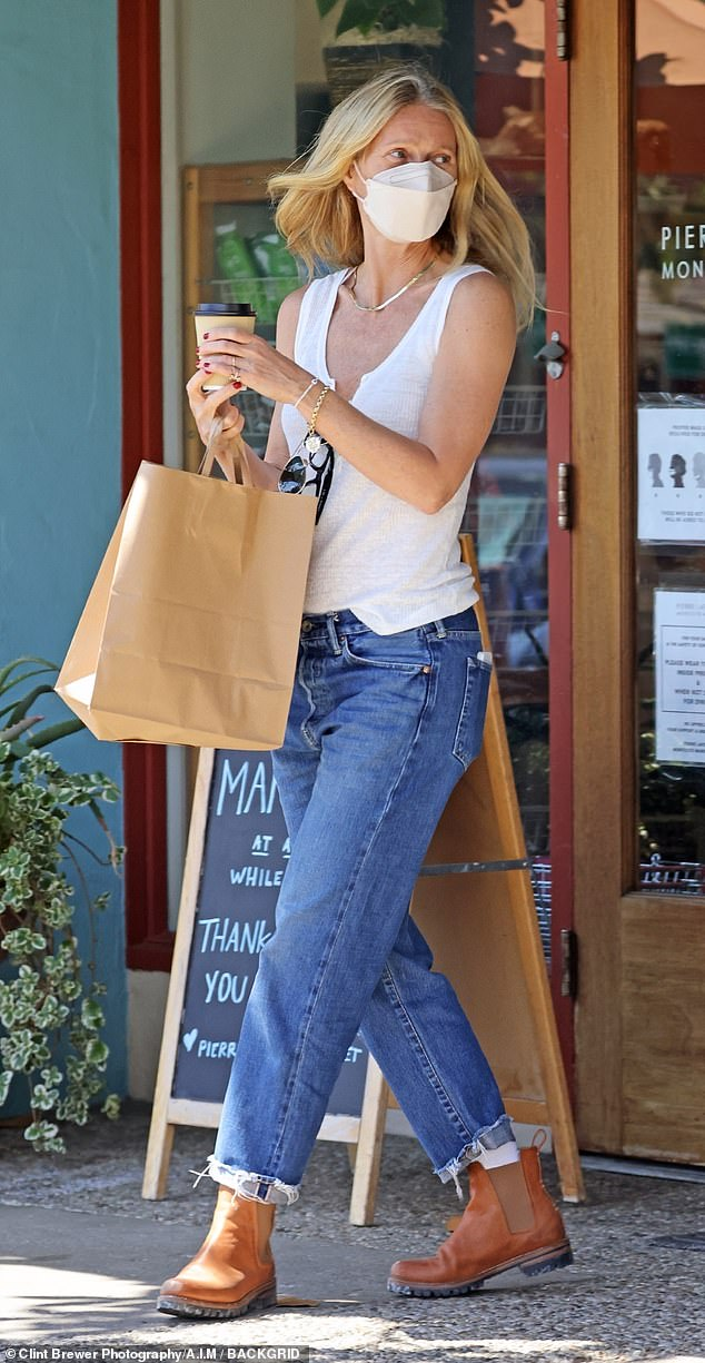 Summer casual: Paltrow, 48, wore a white tank top and blue jeans with distressed hems for her errand. She stepped out in brown slip-on ankle boots and donned a face mask