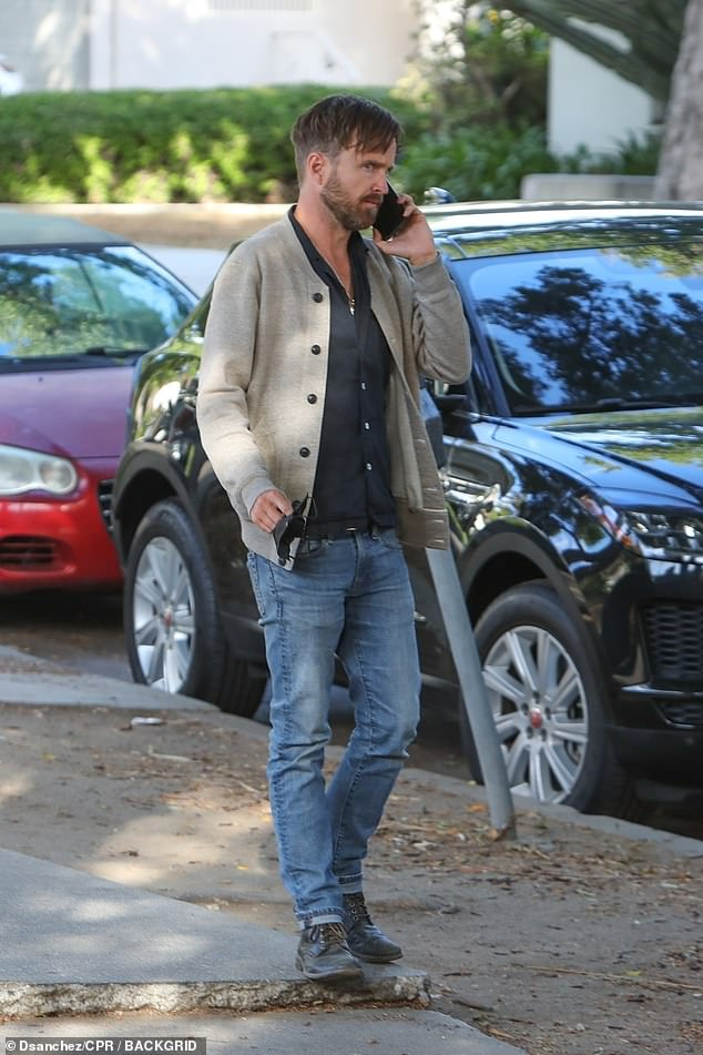 Keeping it casual: Actor Aaron dressed down for the day and was relaxed in a pair of denim jeans and a blue shirt with a light jumper on top, while he wore blue suede shoes on his feet