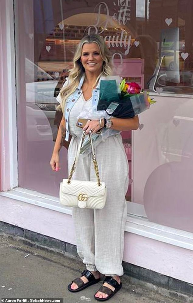 Looking good: Kerry donned a cream jumpsuit teamed with a denim waistcoat and accessorised with a pair of brown sandals and a Gucci handbag