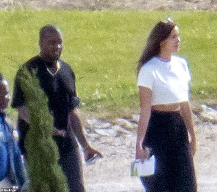Casual couple: Irina looked stunning a white crop top while Kanye went low-key in a black T-shirt as the pair looked every inch of the happy new couple