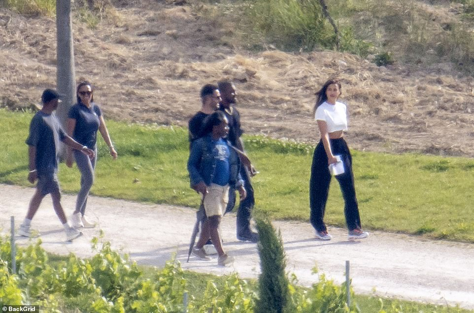 Group fun: Kanye could be smiling as he gazed towards Irina on their walk
