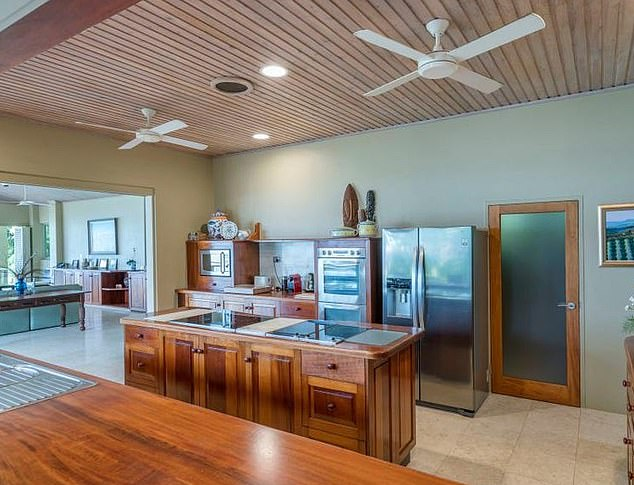 Tropical oasis: It also has a gorgeous cliff-top garden featuring palm trees and plenty of trees that overlook the water. The kitchen is pictured