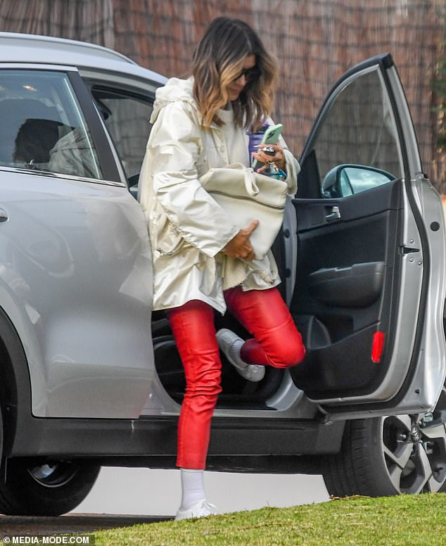 Glam: Kate looked stylish with her wearing a pair of red pants which is mixed with a cream wool jumper and a glamorous overcoat