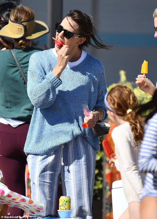 Yum!A stand nearby advertised 'All Natural Popsicles,' so the Alias star picked up a fruity red variety to cool down with