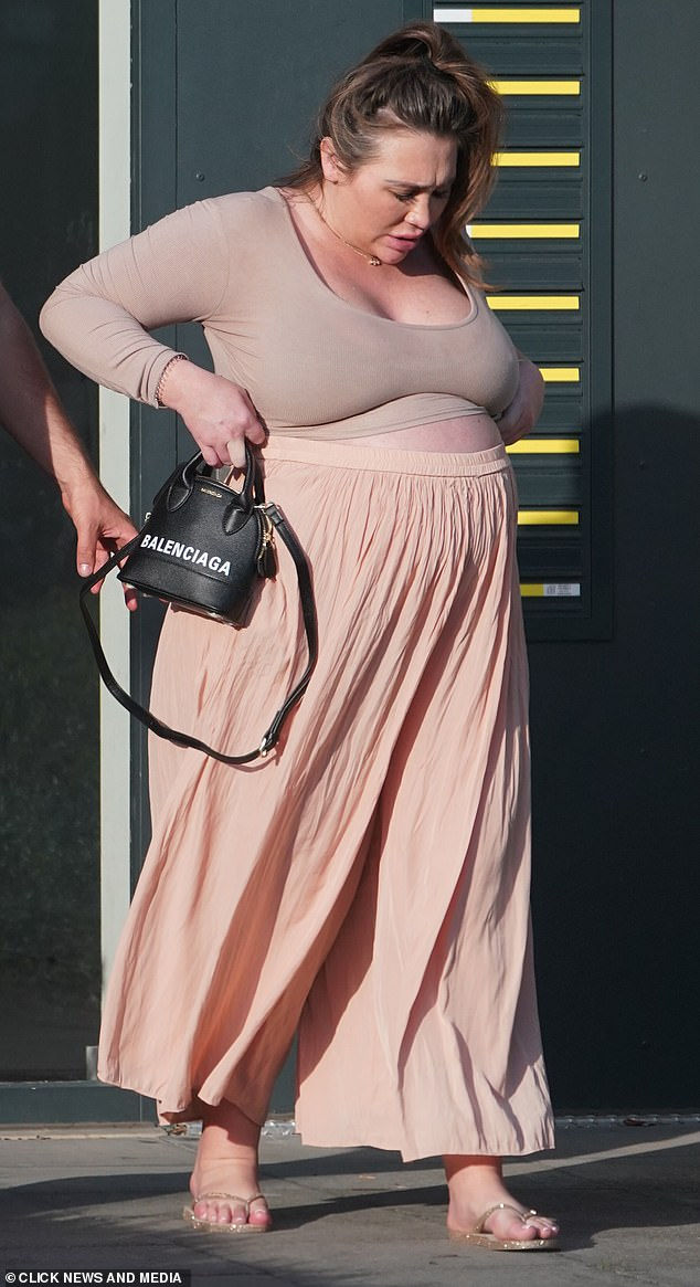 Mummy-to-be:Lauren Goodger displayed her growing baby bump while stepping out in Essex on Tuesday with her boyfriend Charles Drury after visiting a friend