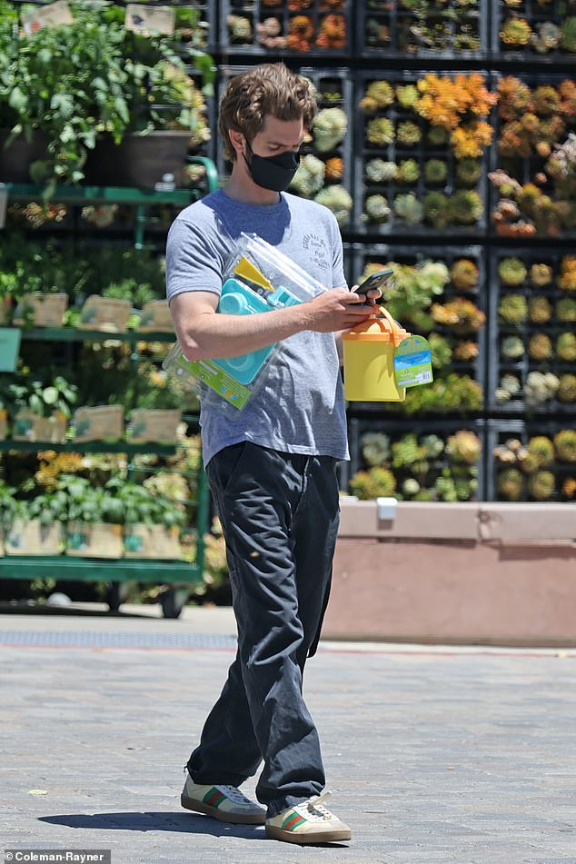 Out and about: Andrew Garfield was glued to his phone when he stepped out in LA on Wednesday ahead of his new role as Christian televangelist Jim Bakker in film The Eyes of Tammy Faye