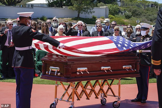 A military honor guard drapes a U.S. flag over the casket of Marine Corps, Pfc. John Franklin Middleswart for a full military honors at Fort Rosecrans National Cemetery, Tuesday, June 8