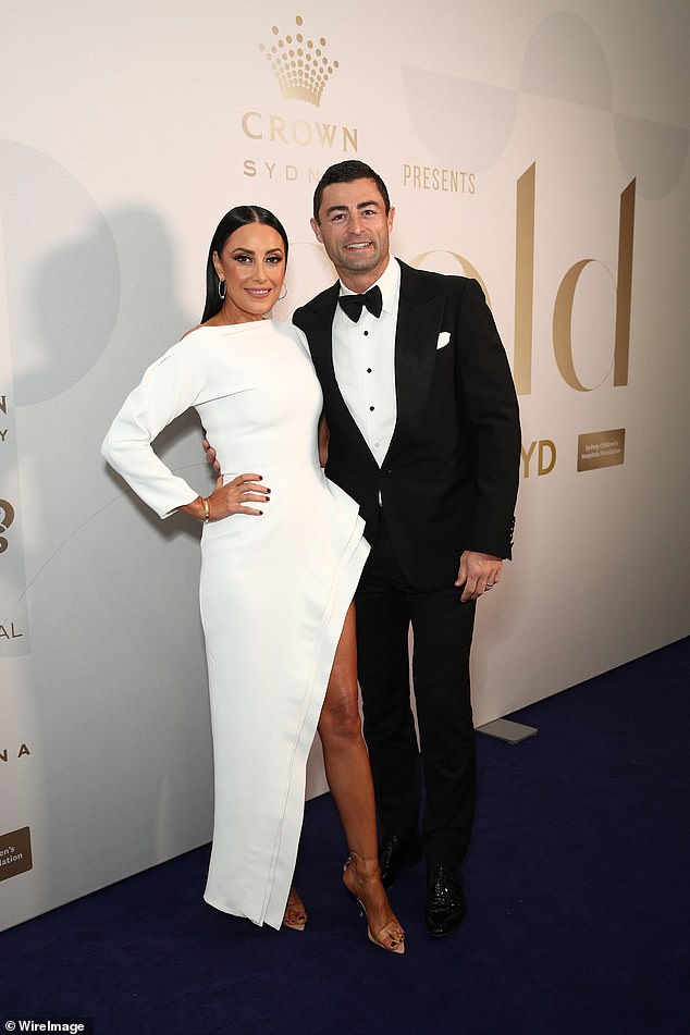 Display on legs!  Terry Biviano (left) turned heads as she showed off her toned pins in a bodycon white dress, complete with a thigh slit as she attended a charity event with husband Anthony Minichiello (right) at Sydney Thursday