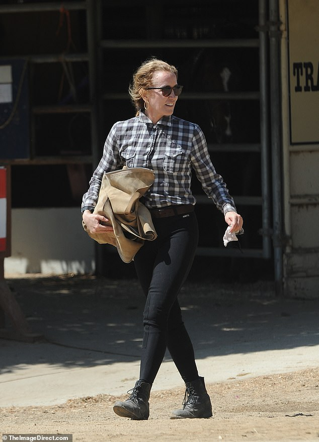 Beaming: Felicity donned a black and white top with brown riding pants, opting for riding boots and helmet