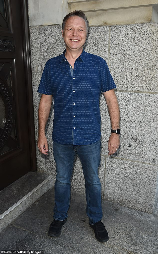 Cool cat:The It's A Sin star donned a navy shirt and jeans