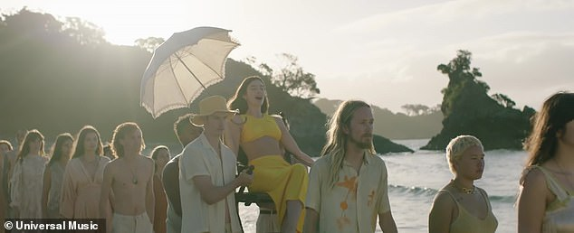 Queen of summer: The singer was also carried on a chair while holding a parasol