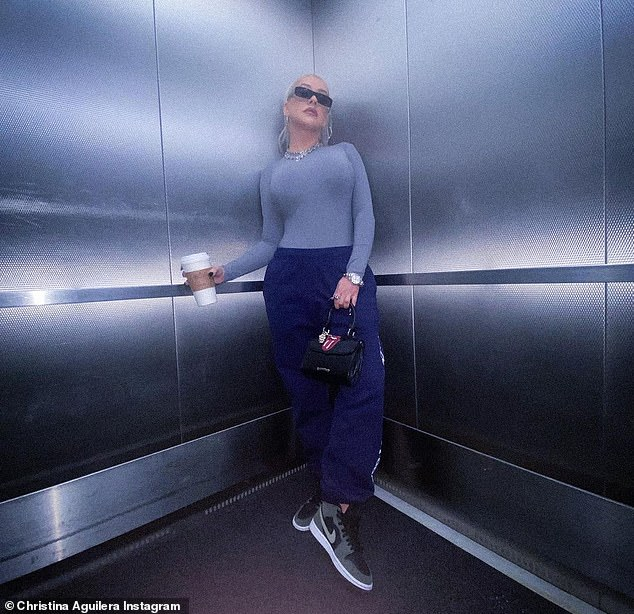 Stylish singer: The hitmaker was seen wearing a form-hugging light blue long-sleeve t-shirt about a darker pair of sweat pants and a set of multi-coloured Nike sneakers