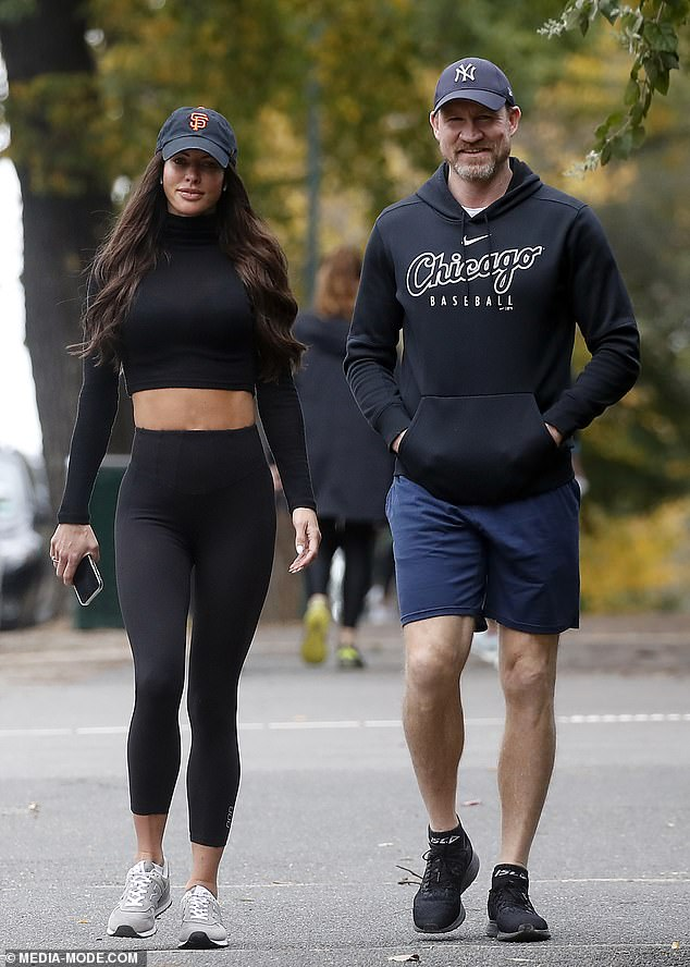 WAG life: The 44-year-old girlfriend of outgoing Collingwood coach Nathan Buckley (right) was visiting her beau when she took off her baseball cap, leaving her extensions tape exposed