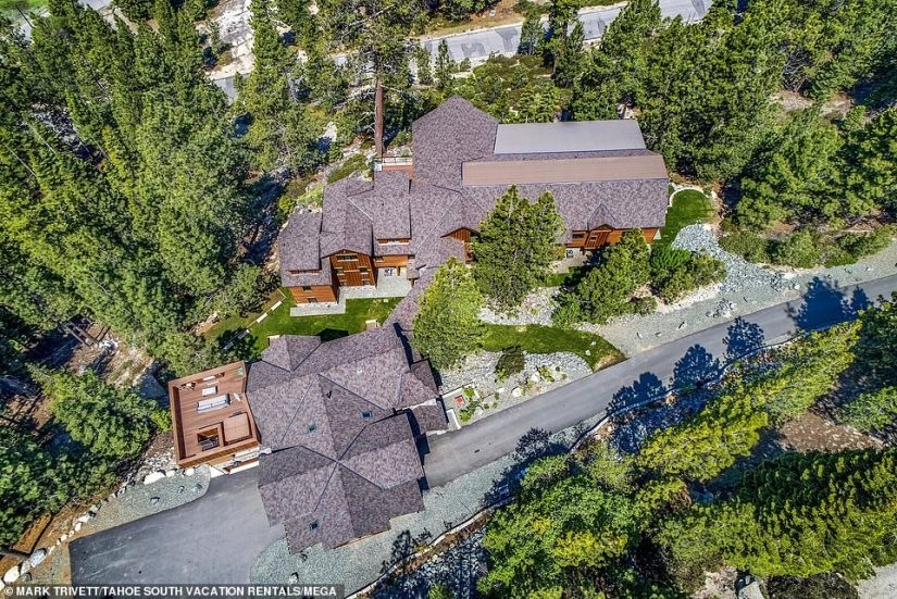 The huge Southern California mansion in the skiing area is flanked by trees