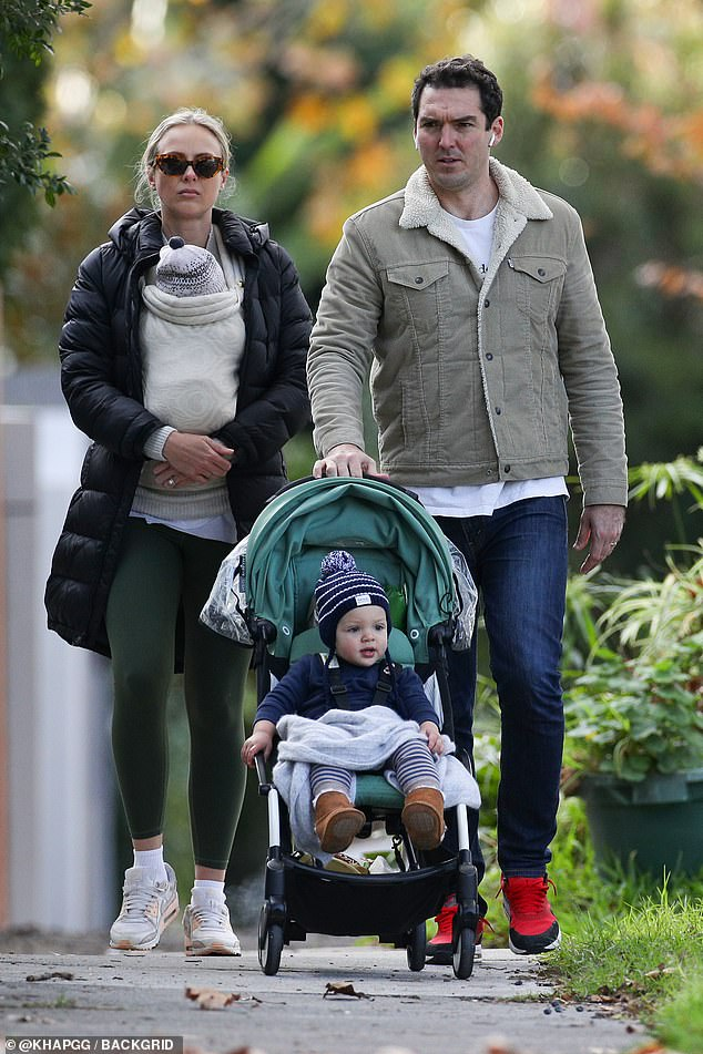Busy, busy:Sylvia cradled baby Henry in a sling attached to her chest while Peter pushed the pram while checking his iPhone