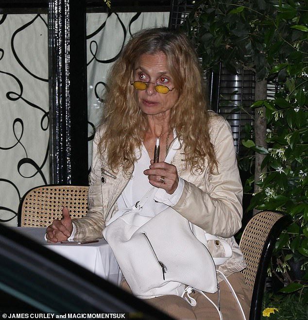Dinner out: Maryam puffed on a vape as she sat at her outdoor table where she donned yellow-tinted glasses