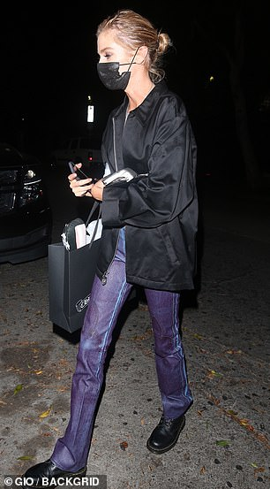Stylish: The model wore nothing but a skinny black bra under a satin bomber jacket while enjoying a night out with friends, also opting for a pair of dark wash bootleg jeans
