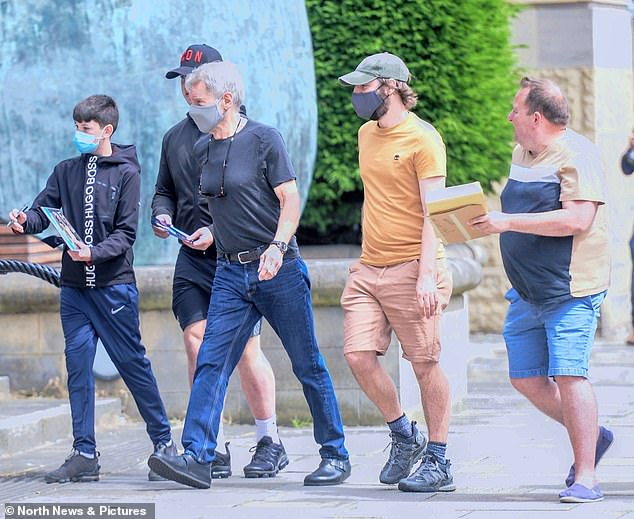 Back to work!  Harrison was seen wearing a simple black t-shirt tucked into a pair of blue denim jeans with a belt tied around his waist