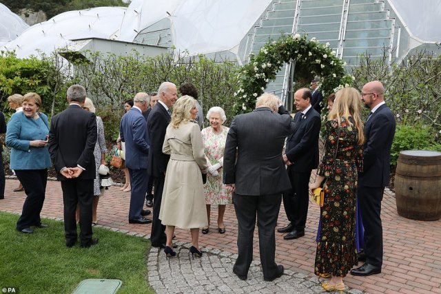 The G7 leaders and spouses gather around the Queen after the leaders took a photo with the monarch