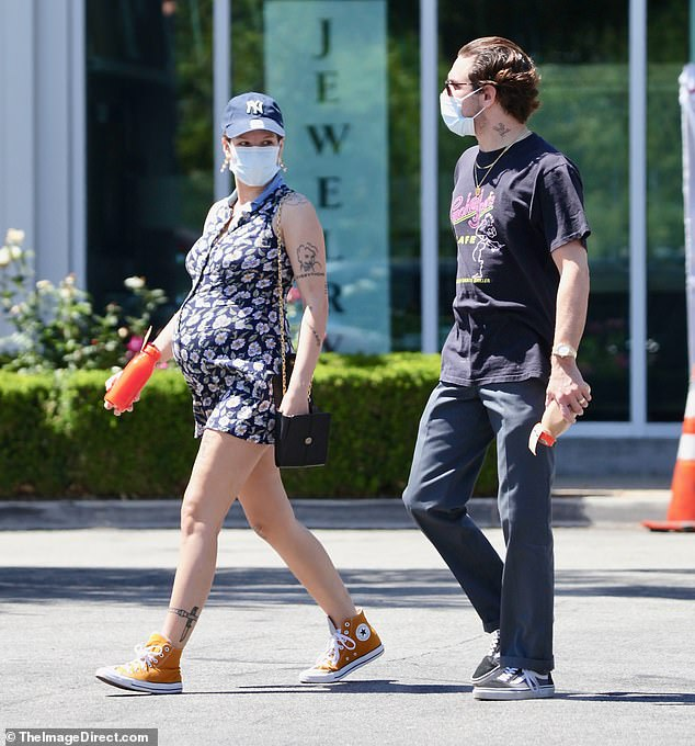 Happy couple:Alongside her was her screenwriter boyfriend (and father to be) who was dressed down in grey slacks, Vans trainers and a black graphic T-shirt
