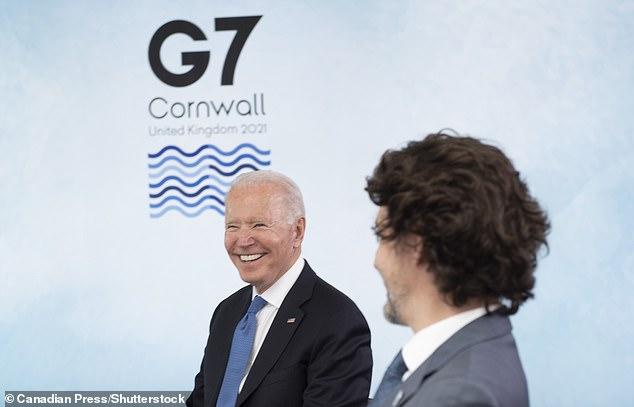 President Joe Biden (left) grins as he sits alongside Canadian Prime Minister Justin Trudeau (right)