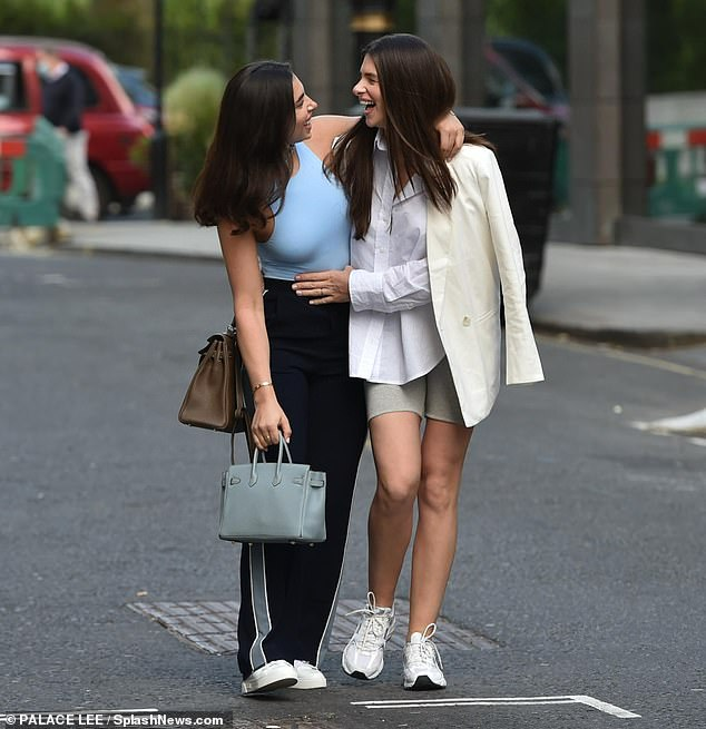 Sweet: Fransesca, who cuddled up to her sister as she headed out in London, carried a pastel blue handbag for the outing and wore a pair of bright white trainers