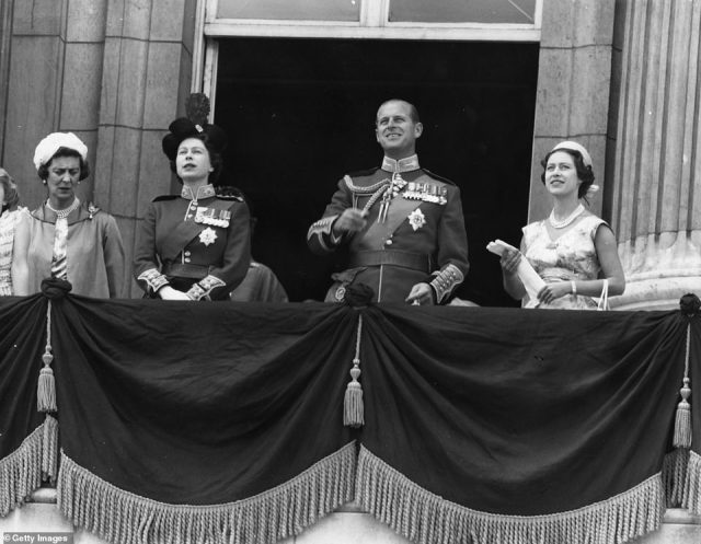 1959 — TAKING IN THE SIGHTS: Queen Elizabeth, then 33, is joined by the Duchess of Kent (left), as well as Prince Philip and Princess Margaret (right) as they watch an RAF flypast from the view of the balcony at Buckingham Palace for the Trooping the Colour.