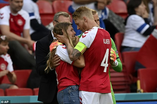 The defender also consoled Eriksen's wifeSabrina Kvist (left) when she came to the pitch