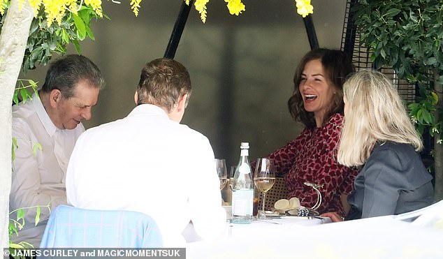 Holding court:Trinny appeared in great spirits as she happily chatted to businessman partner Charles and other pals