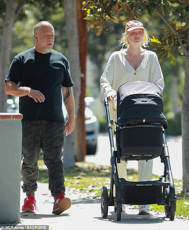 Daily walk: Elsa Hosk, 32, brought along a male friend when she headed out for a stroll with her four-month-old daughterTuulikki in Pasadena on Saturday