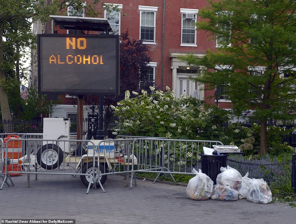 The NYPD has put up a sign reading 'no alcohol' in Washington Square Park even as the city fails to enforce curfews